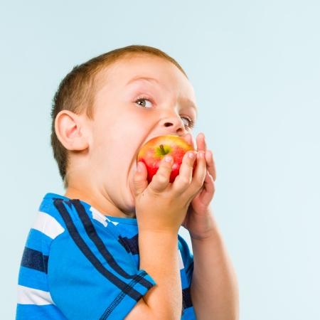Little boy on striped t-shirt eating apple, studio shot and light blue background Stock Photo - 22442590