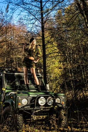 Beautiful girl on camouflage outfit with machete, she standing top of the off-road vehicle bonnet photo