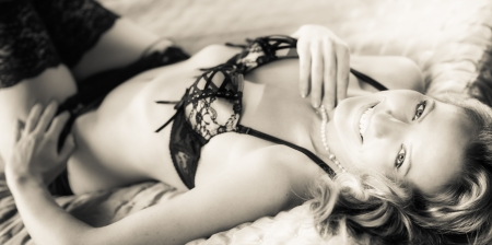 Smiling  woman in lingerie, lying on bed, tinted black and white image photo