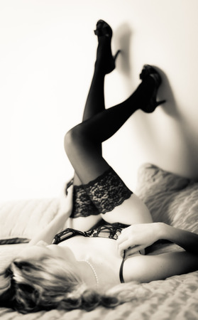 Beautiful woman in lingerie and high heels, lying on bed, tinted black and white image Stock Photo