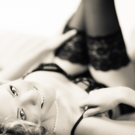 Smiling  woman in lingerie, lying on bed, tinted black and white image Standard-Bild