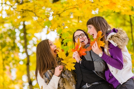 kindred: Three sisters have a fun together on autumnal park Stock Photo