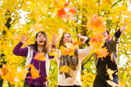 kindred: Three sisters throwing maple leaves on autumnal park Stock Photo