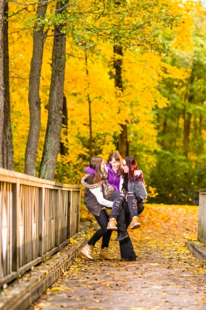 pranks: Three sisters play pranks on bridge and they have a fun together on autumnal park Stock Photo