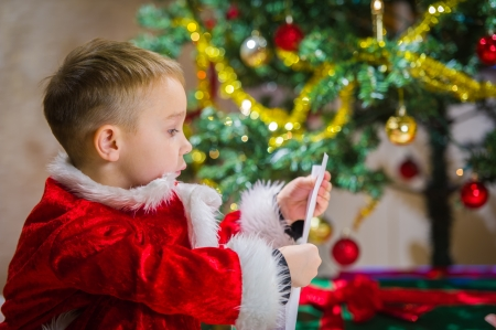 Adorable 5 year old boy check over him letter to Santa Claus, Christmas tree on background photo
