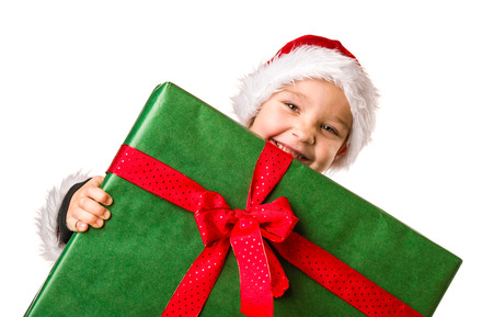 christmassy: Adorable 5 year old boy wearing Santa Claus costume, large Christmas gift, white background Stock Photo