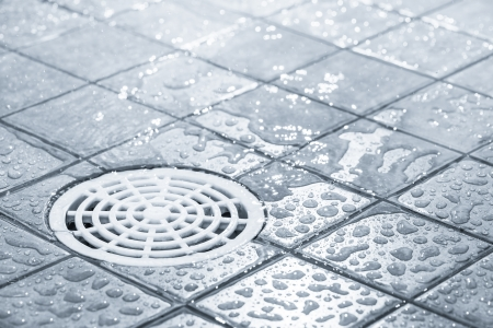 Floor drain, running water in shower, tinted black and white image 版權商用圖片