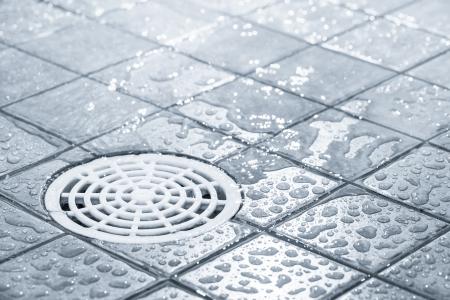 Floor drain, stromend water in de douche, getinte zwart-wit beeld Stockfoto
