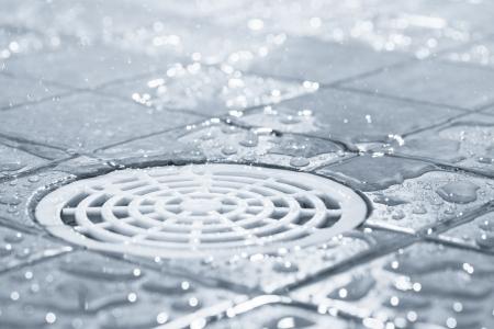 riool: Floor drain, stromend water in de douche, getinte zwart-wit beeld Stockfoto
