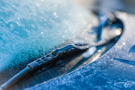 Frozen windshield, cold weather, sunlight on backlight, focus on foreground Stock Photo