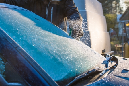 scraping: A man cleans frozen windshield by scratching, cold morning