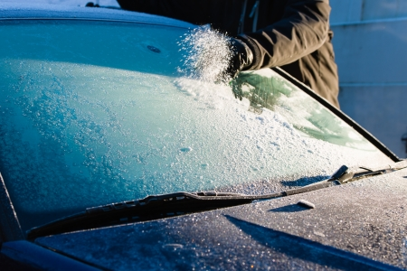 A man cleans frozen windshield by scratching, cold morning