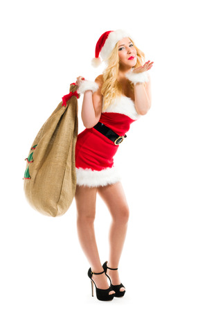 Attractive girl wearing on Santa Claus costume and holds Christmas sack, full length composition and white background photo