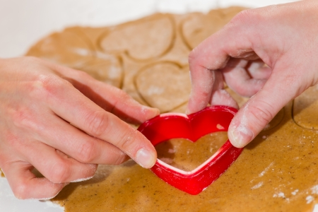 Lesbian couple uses heart gingerbread mould together photo