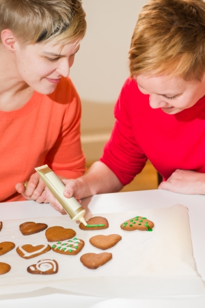 decorates: Lovely lesbian couple makes gingerbread and decorates them Stock Photo