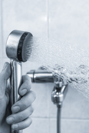 A man holds open shower mixer in bathroom, tinted black and white image, vertical format Stock Photo - 24698140