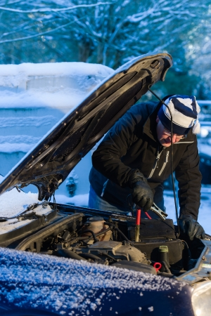A man hook up booster cables to the discharged battery, cold winter day Standard-Bild