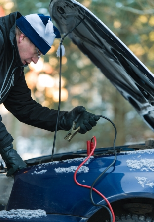 hook up: A man hook up booster cables to the discharged battery in cold winter day Stock Photo