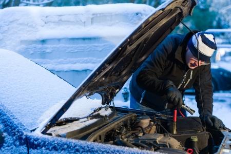 Een man aansluiten startkabels om de lege accu, koude winterdag