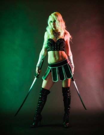 Performer woman wearing sexy costume and holding a samurai sword, grey smoky background photo