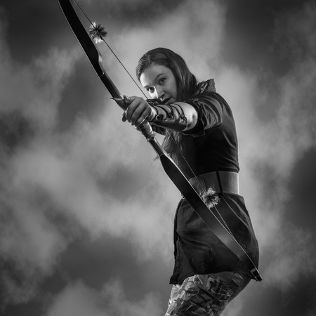 Beautiful archery woman aiming, sky on , black and white image photo