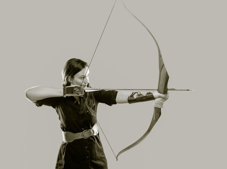 Beautiful archery woman aiming, tinted black and white image 版權商用圖片