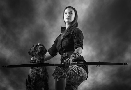 Beautiful archery woman and dog, sky on , black and white image photo