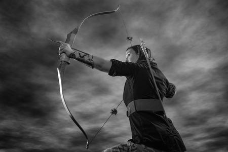 les arcs: Belle femme de tir � l'arc vise, sur le ciel, image en noir et blanc Banque d'images