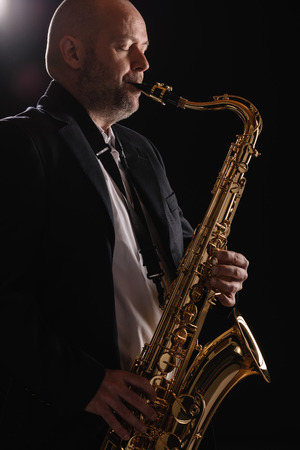 Adult musician playing tenor saxophone eyes closed, dark background