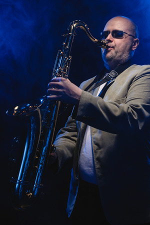 Adult musician playing tenor saxophone, blue smoky background photo