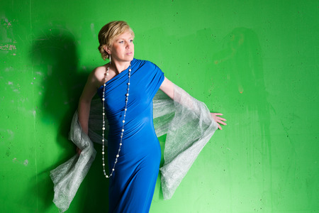 woman scarf: Mature woman wearing blue dress and posing, green concrete wall on background Stock Photo