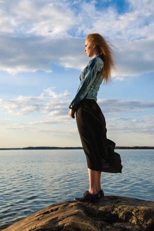 twiggy: Beautiful young woman looks at the horizon on shore - wind blowing and cloudy sky