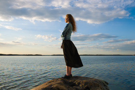 Beautiful young woman looks at the horizon on shore - wind blowing and cloudy sky