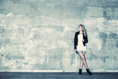 fashion girl: Beautiful urban girl leans against a concrete wall, cross processed image