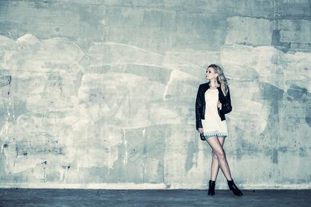 moda: Menina urbana bonita inclina-se contra uma parede de concreto, imagem Cruz processados