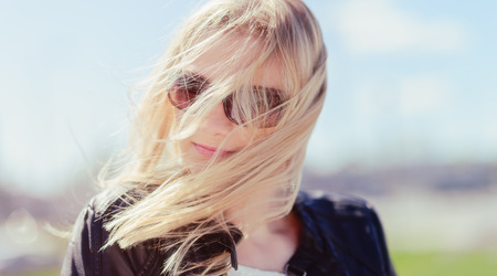 Closeup, fashionable beautiful young blond wearing a leather jacket, windy and warm sunny day photo