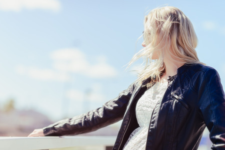 Fashionable beautiful young blond wearing a leather jacket, warm sunny day photo