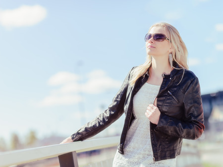 Fashionable beautiful young blond wearing a leather jacket, warm sunny day