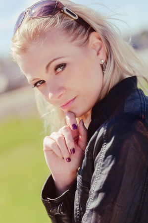Close up, fashionable beautiful young blond wearing a leather jacket, warm sunny day photo