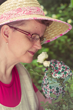 cross processed: Mature woman sniffing the white rose in the garden, cross processed image