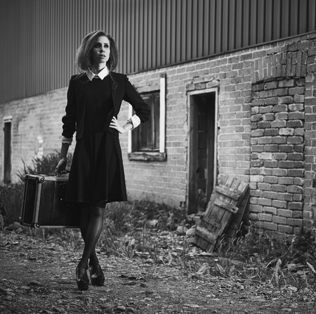 Fashionable young woman with her suitcase, old rural scene, black and white image photo