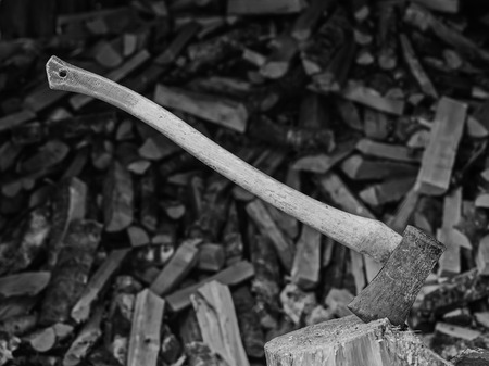 An axe and the woodpile, black and white image photo