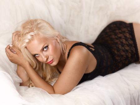 Schöne blonde Frau mit schwarzen Körper und auf der Couch liegen