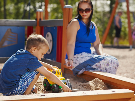 Mother and six year old boy child play together in sandbox photo