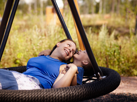 Mother and six year old boy child sitting together on the swing photo