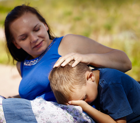 A mother comforts her son, which is little hurt photo