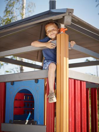 six year old: Six year old boy climbing on playground Stock Photo