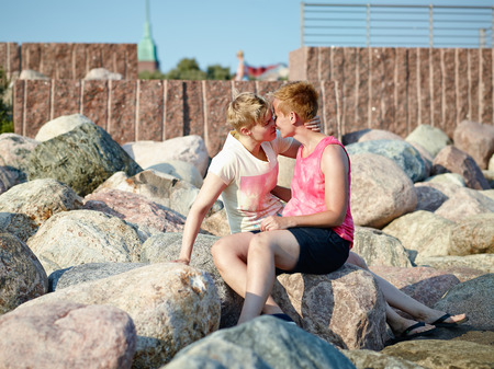 housemate: Women couple sits together on rocks in the afternoon