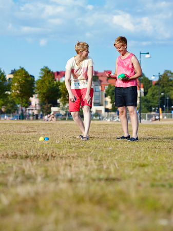 housemate: Two women play petanque in the park in the afternoon sunlight, city on background