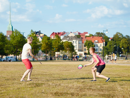 housemate: Two women play summer game in the park in the afternoon sunlight, city on background